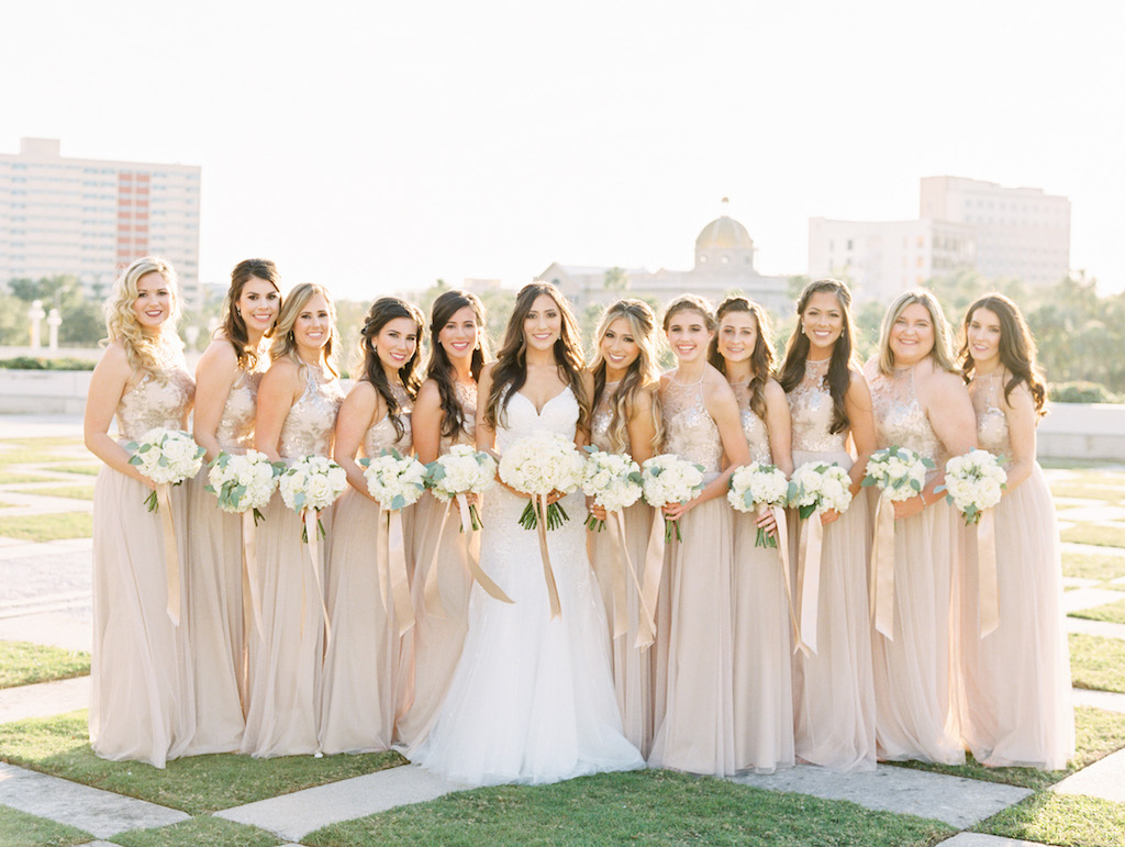 Outdoor Downtown Tampa Park Bridal Party Wedding Portrait, Bridesmaids in Floral Lace Illusion Halter Champagne Amsale Dresses, with White Floral and Greenery Bouquet with Champagne Ribbon, Bride in Princess Neckline Tatiana Martina Dress | Tampa Dress Shop Bella Bridesmaids