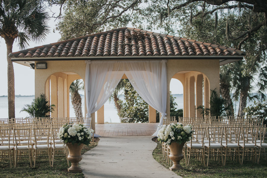 Outdoor Southern Waterfront Wedding Ceremony with Gold Chiavari Chairs, Large Classical Planters with White FLoral and Greenery, and White Draping Ceremony Arch in Gazebo | Bradenton Wedding Venue Powel Crosley Estate