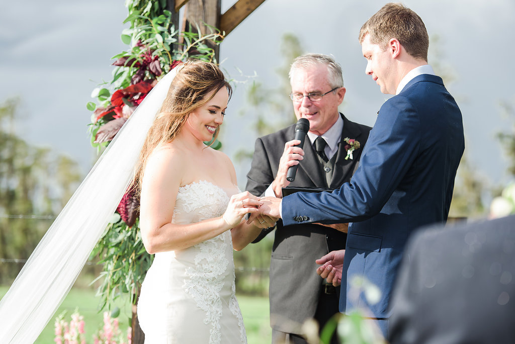 Outdoor Farm Wedding Ceremony Portrait, Bride in Sweetheart Strapless Lace Ines Di Santo Dress, Groom in Navy Blue Suit Men's Wearhouse Suit, with Wooden Ceremony Arch with Marsala Red Florals and Greenery