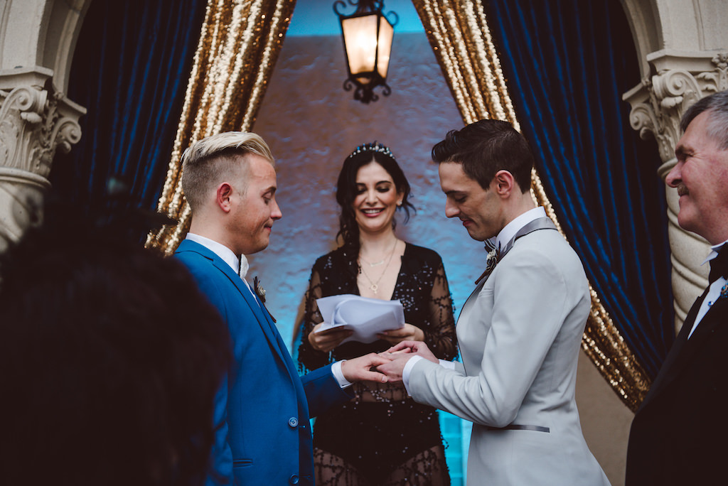 Vintage Glam Inspired Same Sex Wedding Ceremony Portrait, Groom in Light Gray Tux and Royal Blue Tuxedo, Celebrant / Officiant in Sheer Sequin Black Dress with Tiara, With Blue and Gold Velvet Draping