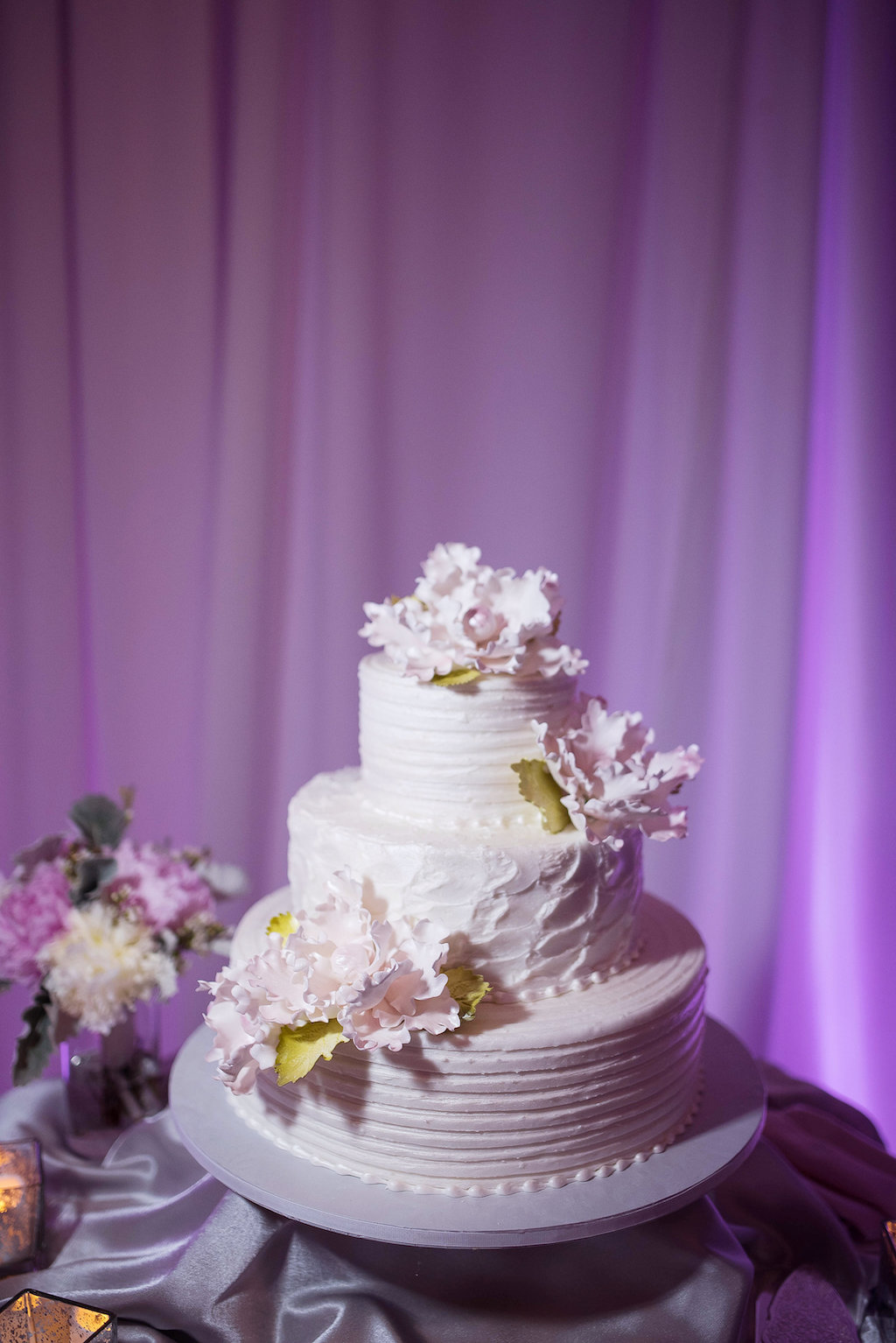 Three Tirered Round White Wedding Cake with Pink Paper Flowers with Gold LEaf Greenery on Gray Cake Stand, with Satin Table LInens White Draping and Purple Uplighting