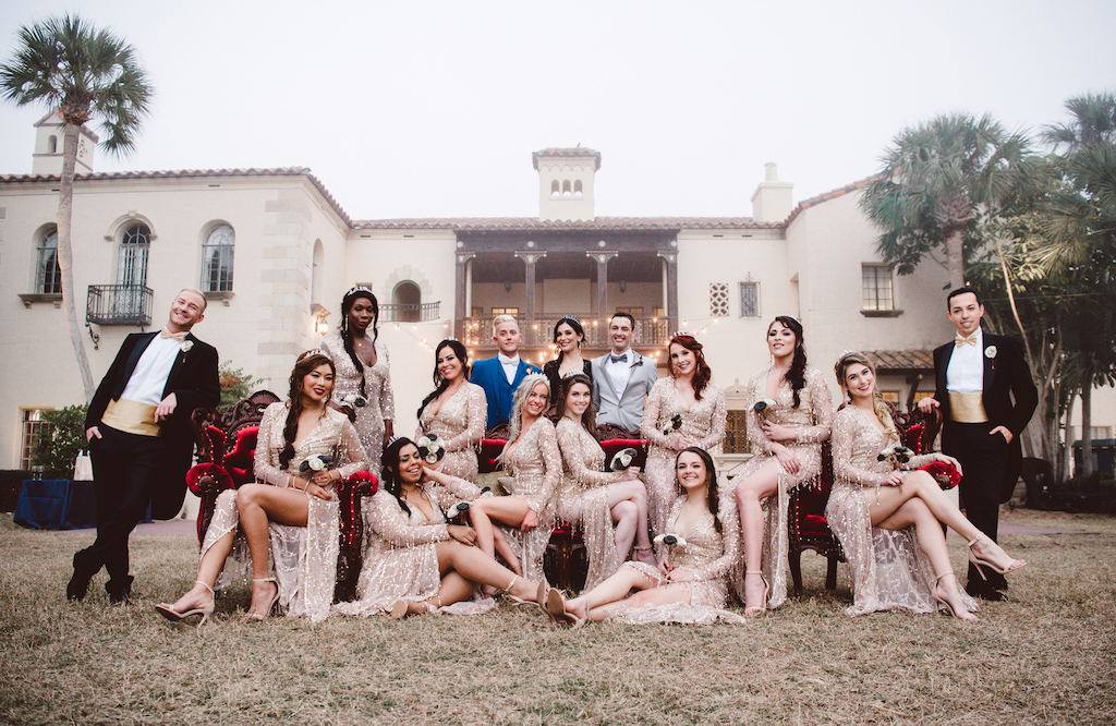 Outdoor Vintage Glam Gatsby Inspired Same Sex Gay Wedding Party Portrait, Bridesmaids in V Neck Lon Sleeve Gold Sequin Pretty Little Things Dresses with Strappy Sandal Wedding Shoes and Silver Tiaras, on Red Velvet Antique Chairs, with Black and White Paper Flower Bouquets, Groomsmen in Black Dress Coats with Gold Cummerbund, Groom in Royal Blue and Light Gray Tuxedo   Sarasota Historic Wedding Venue Powel Crosley Estate   Tampa Bay Hair and Makeup LDM Beauty Group