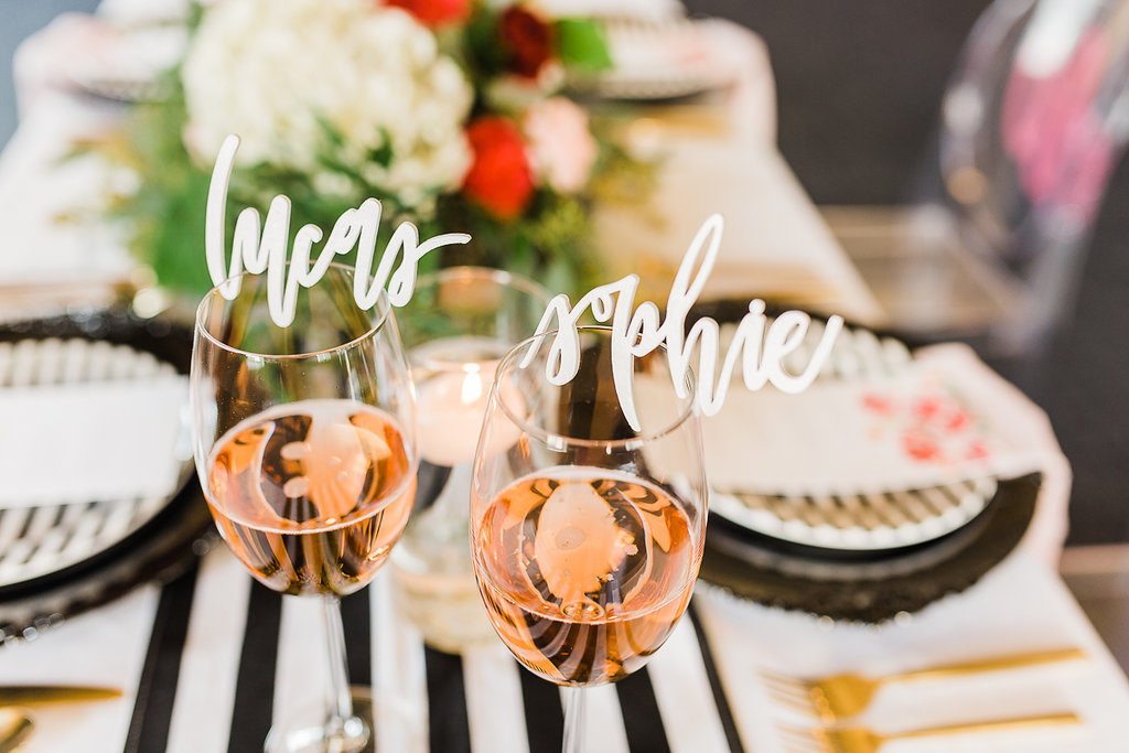 Kate Spade Inspired Wedding Reception Table Decor with White Laser Cut Stylish Script Name Cards Resting on Wine Glasses, with Black Chargers, Black and White Striped Runner, and Gold Flatware | Tampa Bay Wedding Rentals Kate Ryan Linens and Event Rentals