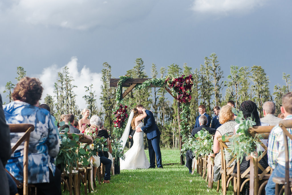 Outdoor Farm Wedding Ceremony First Kiss Portrait, Bride in Sweetheart Strapless Lace Ines Di Santo Dress, Groom in Navy Blue Suit Men's Wearhouse Suit, with Wooden Ceremony Arch with Marsala Red Florals and Greenery, and Wooden Crossback Chairs   Tampa Bay Wedding Planner NK Productions