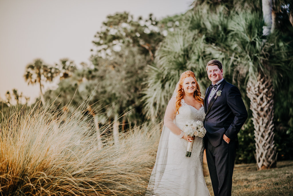 Outdoor Waterfront Wedding Portrait, Bride in Sweetheart Trumpet Lace Long Sleeve Essence of Australia Dress with White Rose Ribbon Wrapped Bouquet, Groom in Midnight Blue Tuxedo with Boutonniere