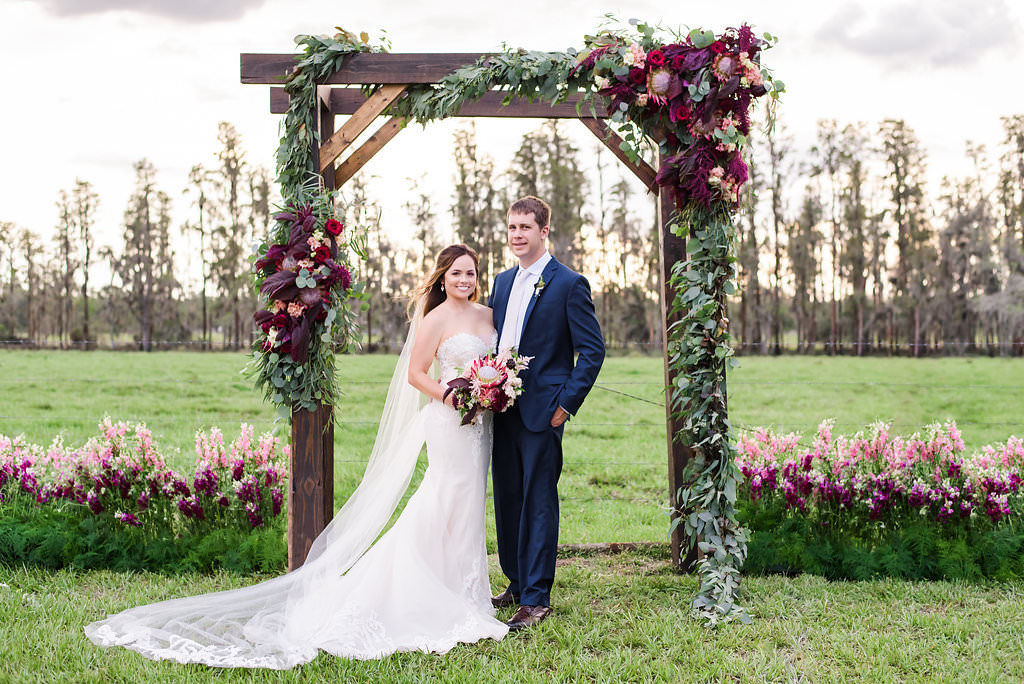Outdoor Farm Wedding Ceremony Portrait, Bride in Sweetheart Strapless Lace Ines Di Santo Dress with Red Protea and Purple Bouquet, Groom in Navy Blue Suit Men's Wearhouse Suit, with Wooden Ceremony Arch with Marsala and Blush Pink Florals and Greenery   Tampa Bay Wedding Planner NK Productions