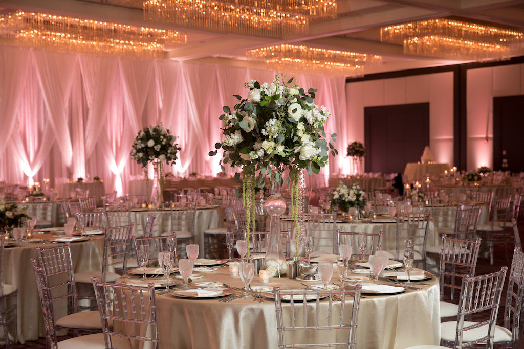 Winter Glam Hotel Ballroom Wedding Reception with Champagne Linens, Clear Chiavari Chairs, and Extra Tall Centerpieces in Geometric Glass Vases with white Floral and Greenery, and White Draping with Blush Pink Uplighting, Silver Chargers | Venue Hilton Tampa Downtown | Rentals Kate Ryan Linen Rentals