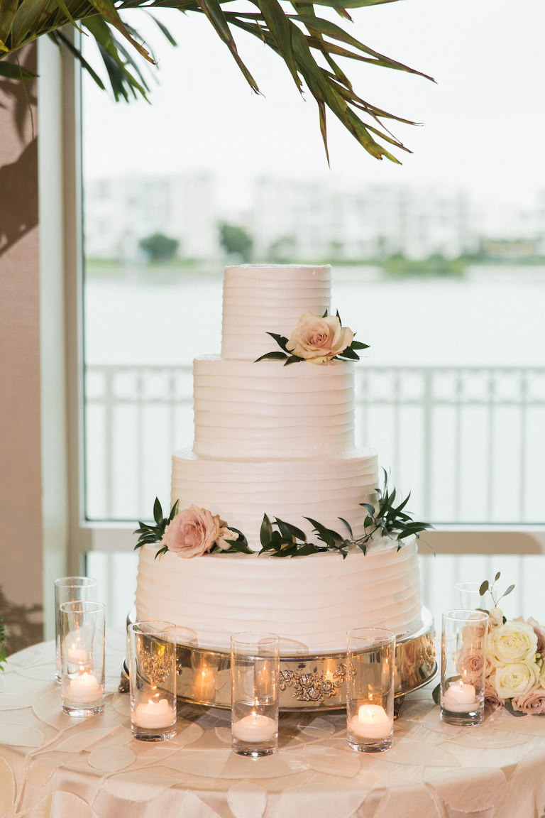 Four Tier Round White Wedding Cake with Blush Pink Rose and Greenery on Antique Silver Cake Stand, with Floating Votive Candles on Textured Blush LInen | Tampa Bay Wedding Caterer Olympia Catering