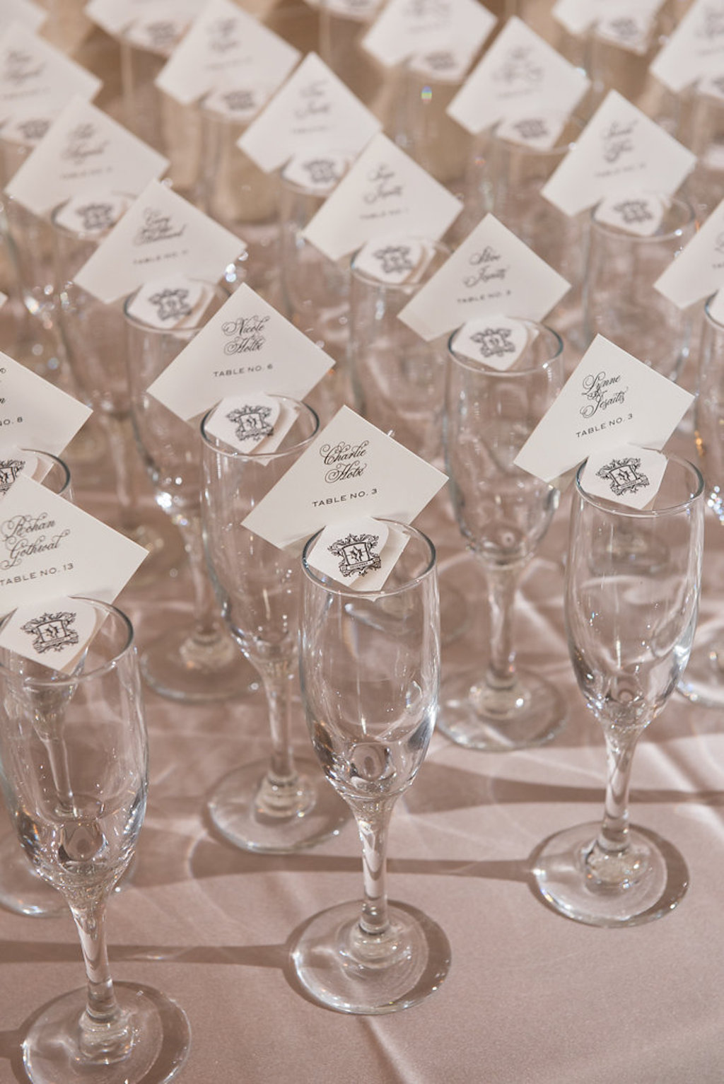 Champagne Glass Escort Card Table with Square White Cards with Elegant Dark Blue Printed Script and Custom Monogram | Sarasota Wedding Stationery and Paper Goods URBANcoast
