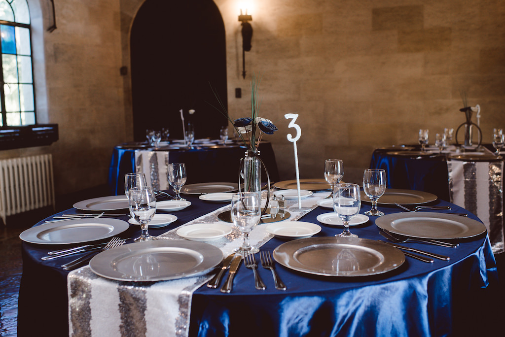 Vintage Glam Wedding Reception Round Table with White and Silver Sequin Runner, Royal Blue Satin Linens and Silver Chargers with Small BLue and WHite Paper Flower Bouquet with Green Grasses in Clear Glass Vase with Silver Table Number   Sarasota Historic Wedding Venue Powel Crosley Estate