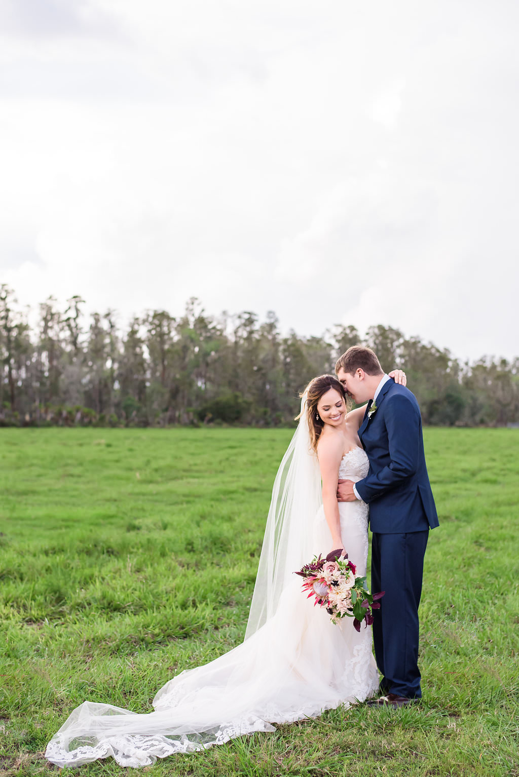 Outdoor Farm Wedding Bride and Groom Portrait, Groom in Navy Blue Suit, with Marsala Red Protea Bouquet with Greenery and BLush Pink Florals