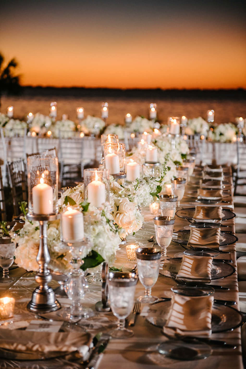 Outdoor Waterfront Sunset Wedding Reception with Long Feasting Tables with Champagne Satin Linens, Low White Floral and Greenery Centerpieces and Silver Candlestickholders and PIllar Candles | Tampa Bay Waterfront Historic Venue Crosley Powel Estate