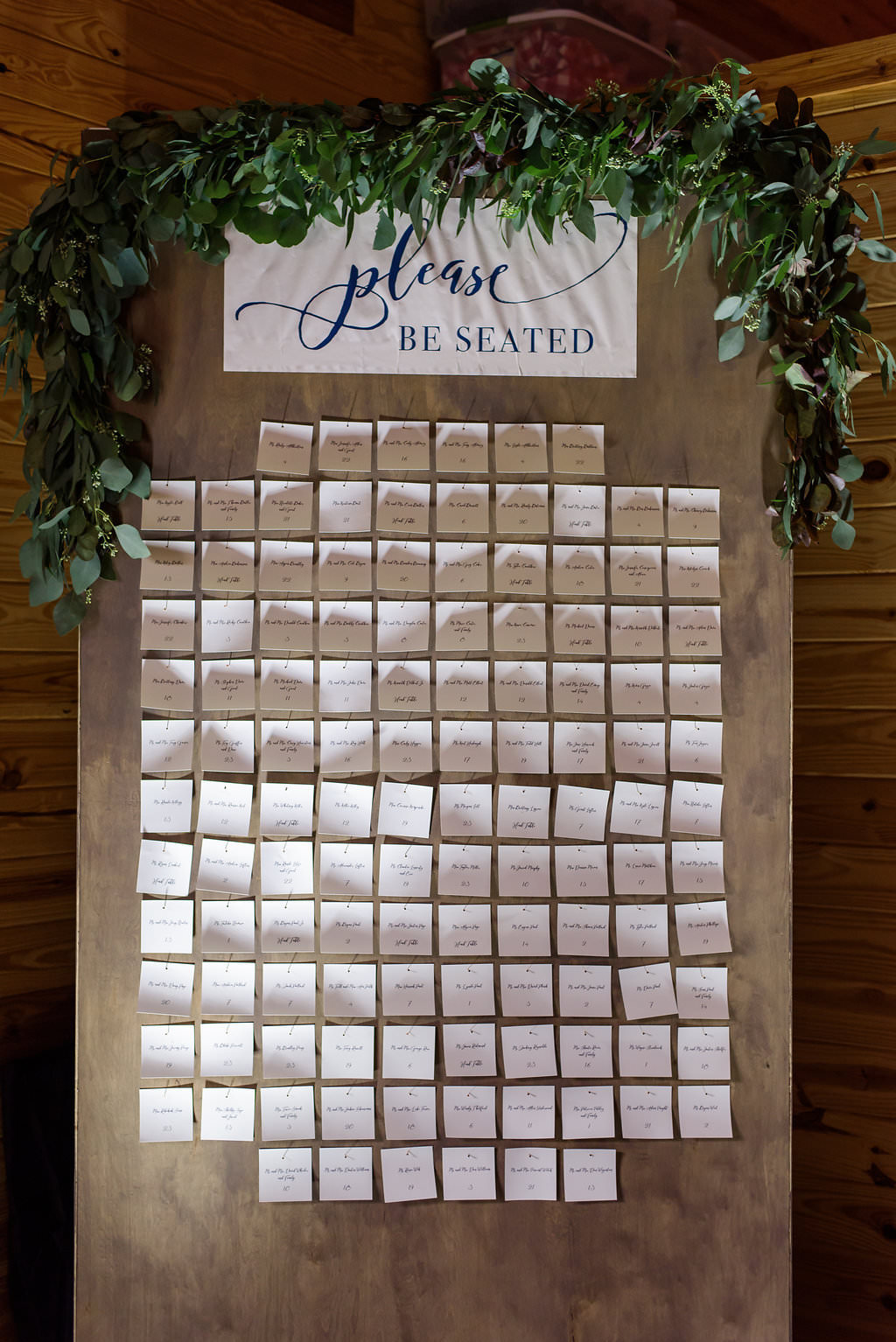 Rustic Wedding Reception Escort Cards on Vertical Board with Greenery Garland and Stylish Navy BLue on White Printed Sign   Tampa Bay Wedding Planner NK Productions