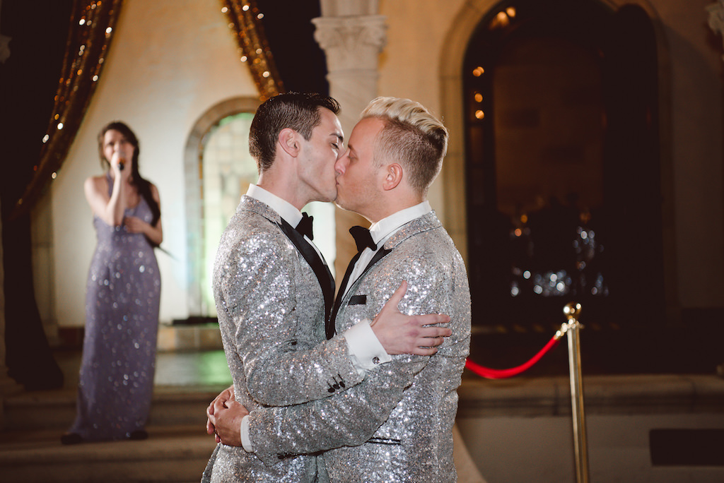 Vintage Glam Gatsby Inspired Same Sex Gay Wedding Reception Portrait in Matching Silver Sequin and Black Tuxedos, with Blue and Gold Velvet Draping
