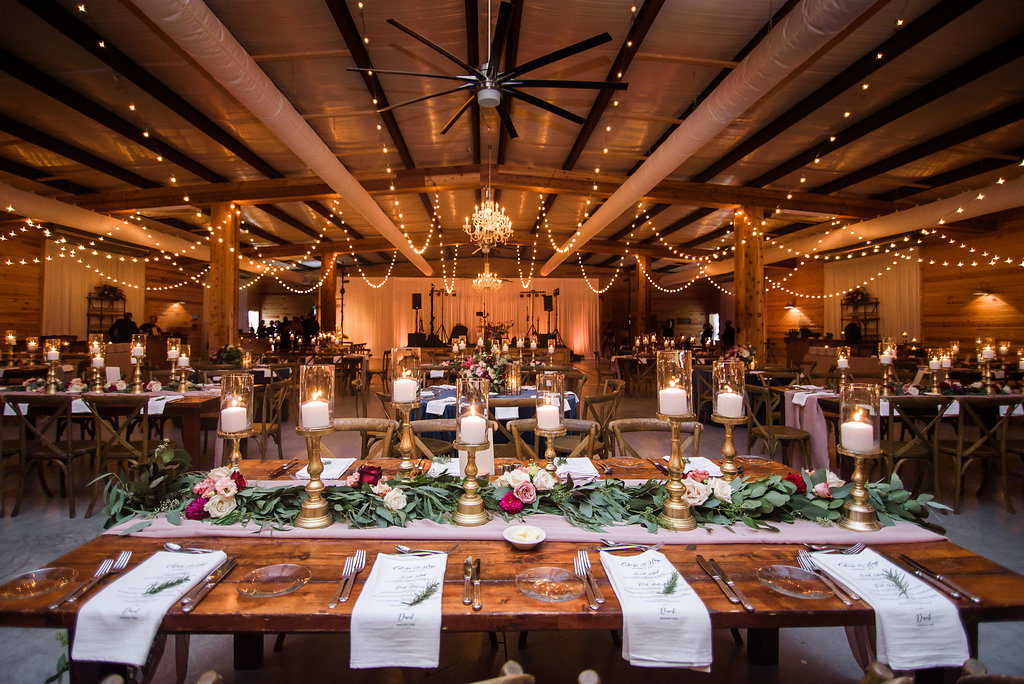 Indoor Rustic Wedding Reception with Wooden Feasting Tables with Greenery Garland Centerpiece and Blush Pink Table Runner, with Marsala Red and BLush Pink Florals, Pillar Candles with Gold Candlestick Holders, White Linens with Rosemary, and String Lights | Tampa Bay Wedding Planner NK Productions