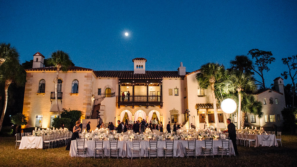Outdoor Waterfront Sunset Wedding Reception with Long Feasting Tables with Champagne Satin Linens, Low White Floral and Greenery Centerpieces and Silver Candlestickholders and PIllar Candles | Tampa Bay Waterfront Historic Venue Crosley Powel Estate | Satin Linens Over the Top Rental Linens
