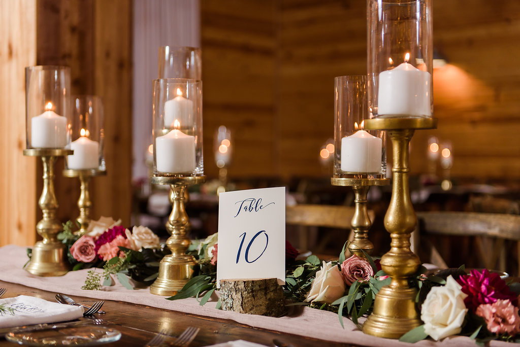 Indoor Rustic Wedding Reception with Wooden Feasting Tables with Greenery Garland Centerpiece and Blush Pink Table Runner, with Marsala Red and BLush Pink Florals, Pillar Candles with Gold Candlestick Holders, White Linens with Rosemary, and Navy Blue Printed on White Table Number in Tree Bark Stand   Tampa Bay Wedding Planner NK Productions