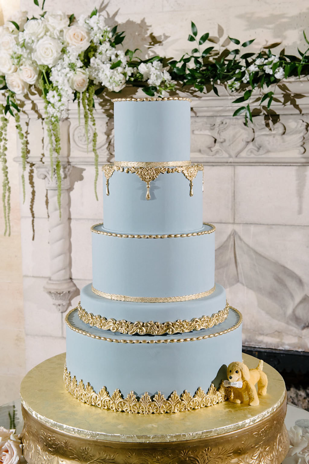 Elegant Powder Blue Five Tier Round Wedding Cake with Gold Details on Cake Stand with Dog Cake Topper and White Florals with Greenery