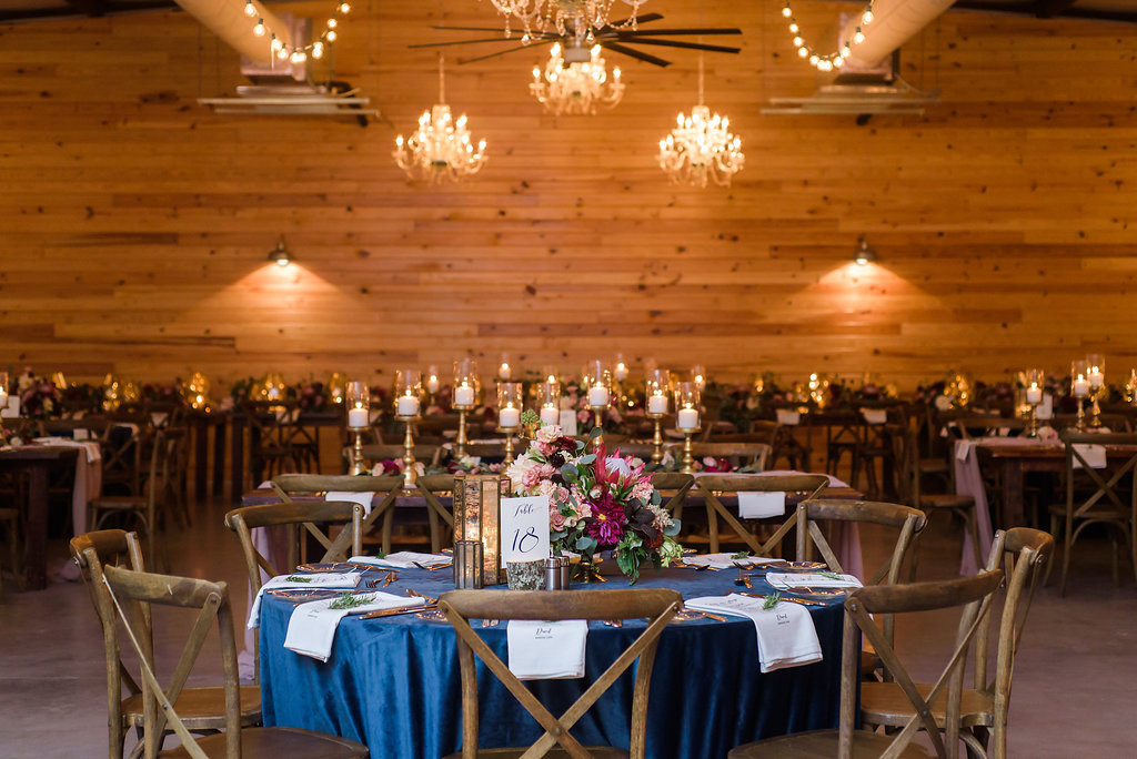 Indoor Rustic Wedding Reception with Round Table with Navy Blue Tablecloth, withMedium Height Centerpiece with Marsala Red and BLush Pink Protea and Florals, Pillar Candles with Gold Candlestick Holders, White Linens with Rosemary, and Navy Blue Printed on White Table Number in Tree Bark Stand, Wooden Cross Back Chairs and Hanging Chandeliers and String Lights   Tampa Bay Wedding Planner NK Productions