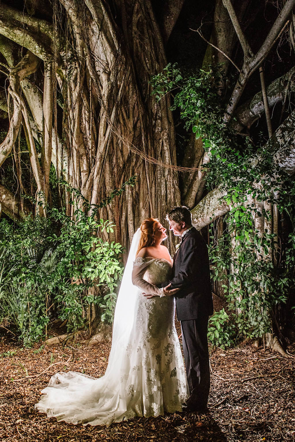 Outdoor Nighttime Wedding Portrait, Bride in Sweetheart Trumpet Lace Long Sleeve Essence of Australia Dress, Groom in Midnight Blue Tuxedo with Boutonniere in Tropical Garden with Banyan Tree