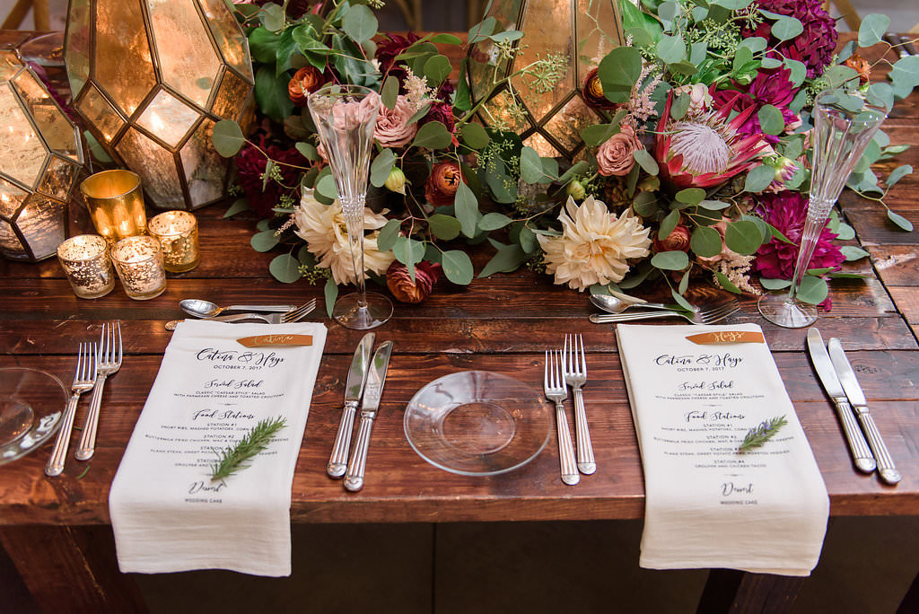 Rustic Wedding Reception Place Setting on Wooden Table with Blue Printed on White Linen Napkin and Menu with Rosemary, Low Centerpiece of Pink Protea, Marsala Red and BLush pInk Florals with Greenery, Geometric Lanterns and Gold Votive Candles   Tampa Bay Wedding Planner NK Productions