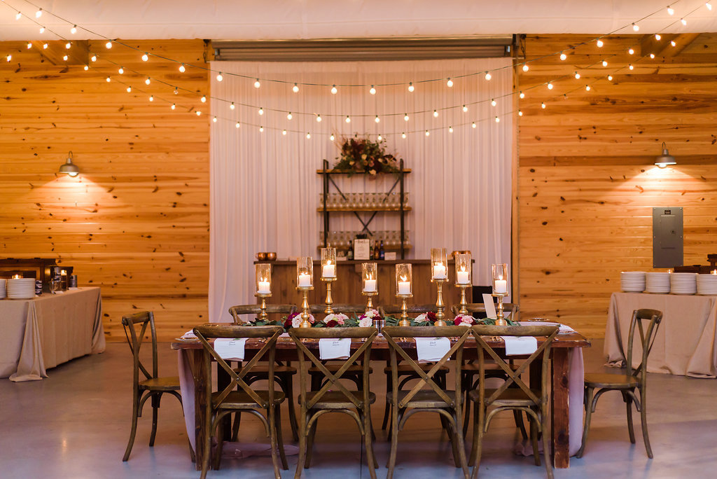 Indoor Rustic Wedding Reception with Wooden Feasting Tables with Greenery Garland Centerpiece and Blush Pink Table Runner, with Marsala Red and BLush Pink Florals, Pillar Candles with Gold Candlestick Holders, White Linens with Rosemary, and String Lights with Cross Back Chairs   Tampa Bay Wedding Planner NK Productions