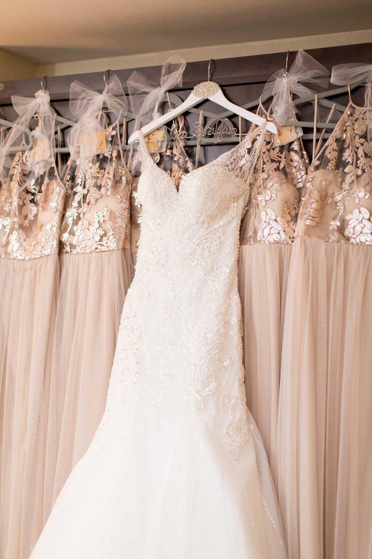 Martina Liana Illusion Lace Princess Cut Wedding Dress on Hanger with Champagne Gold Illusion Lace Amsale Bridesmaids Dresses from Tampa Bay Dress Shop Bella Bridesmaids