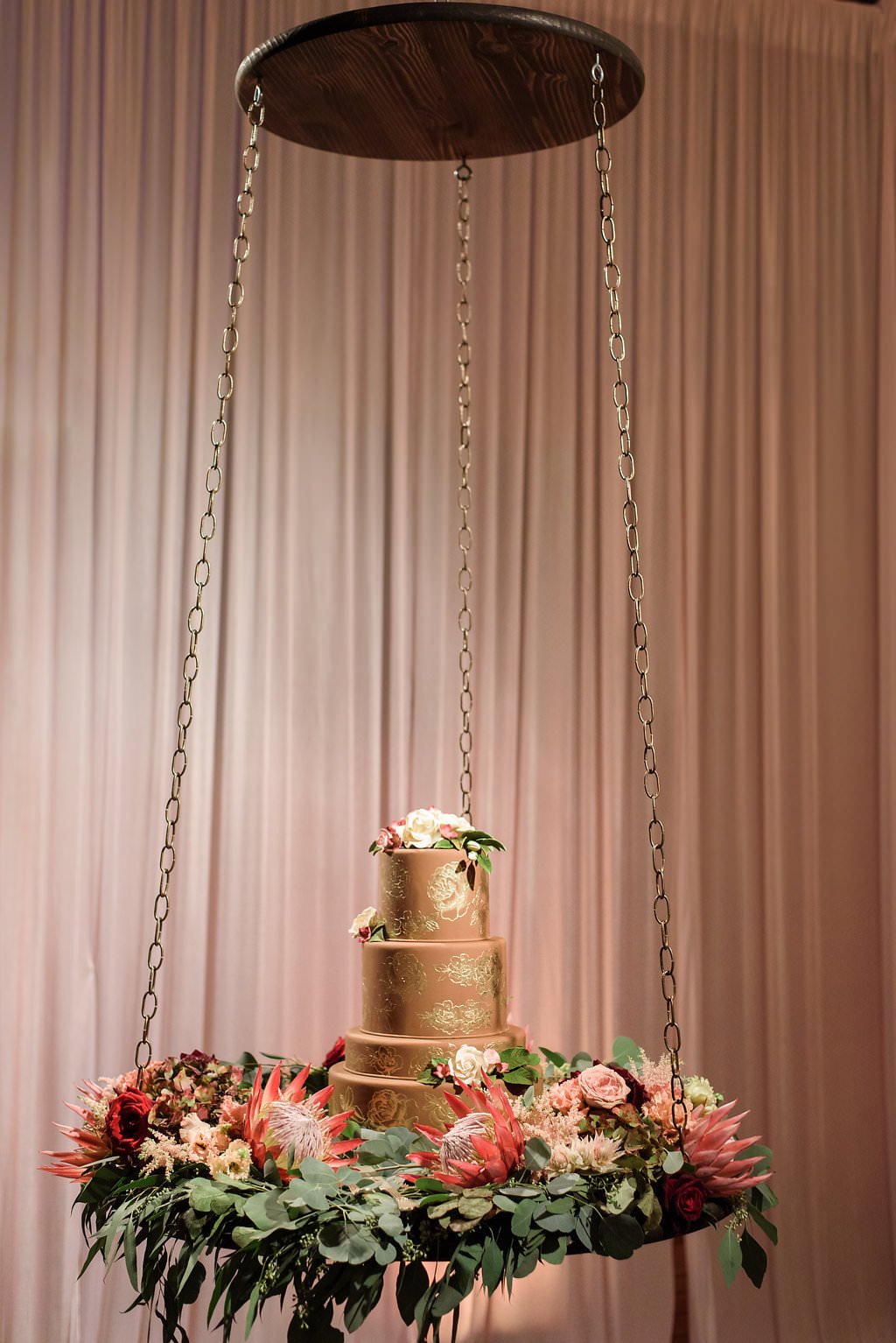 Four Tiered Round Copper and Gold Wedding Cake with Marsala Red Protea, Blush PInk and Cream Florals with Greenery, on Round Wooden Suspended Platform Table Hanging from Chains   Tampa Bay Wedding Planner NK Productions