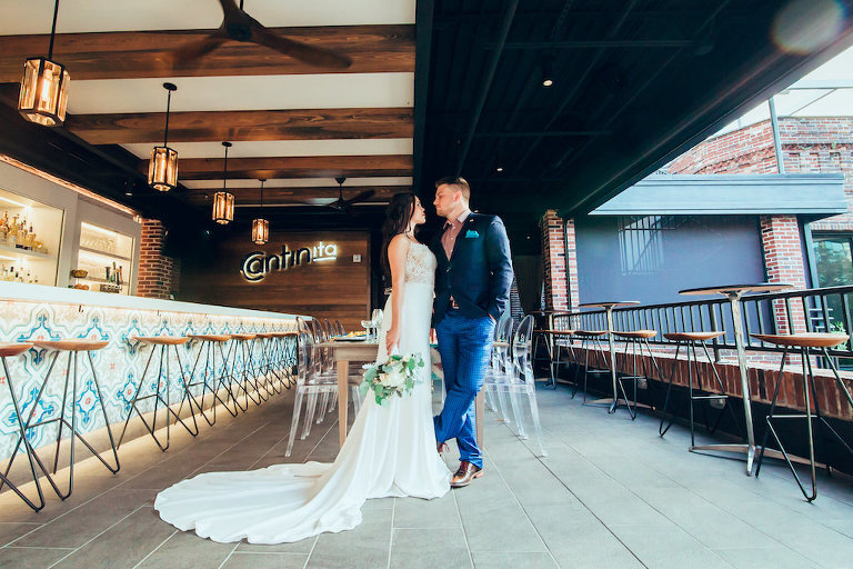 Industrial Chic Intimate Restaurant Bar Wedding Reception Portrait, Bride in Belted Column Dress with Greenery and White Floral Bouquet, Groom in Blue Suit with Pink Shirt | Modern Downtown St Pete Cantina Wedding Venue Red Mesa Events | Jennifer Matteo Event Planning