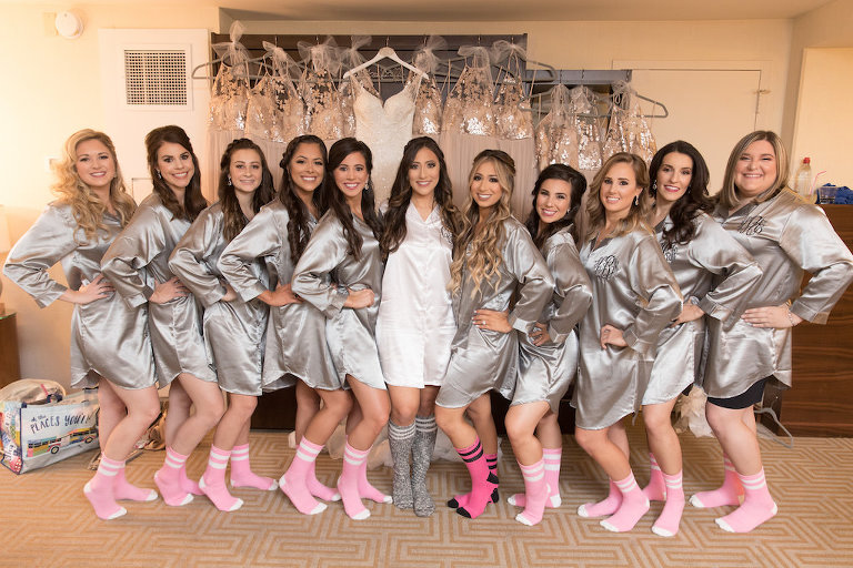 Interior Bridal Party Getting Ready Portrait in Matching Silver Silk Robes with Pink Socks