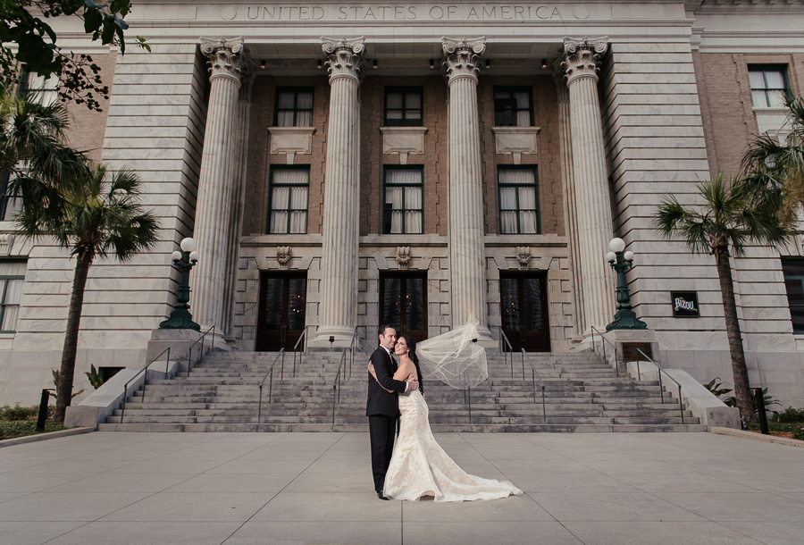 Outdoor Architectural Wedding Portrait, Bride in Floral Champagne Strapless Mermaid Wedding Dress, Groom in Black Tuxedo | Downtown Tampa Historic Hotel Venue Le Meridien