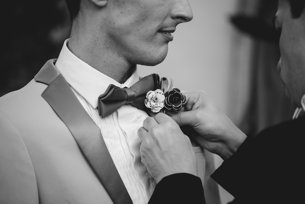 Groom Getting Ready Portrait in Tuxedo with Paper Sheet Music and Black and Glitter Flower and Ribbon Boutonniere
