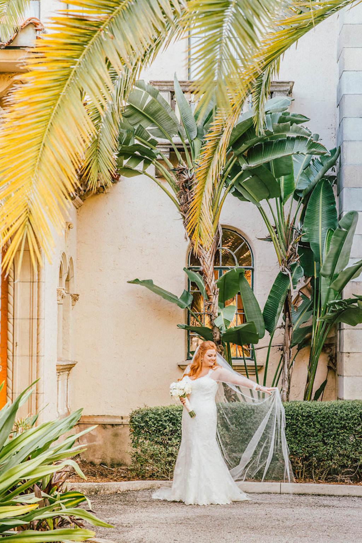 Outdoor Tropical Garden Courtyard Bridal Portrait in Trumpet Essence of Australia Dress with White Rose Bouquet | Sarasota Wedding Venue Crosley Powel Estate