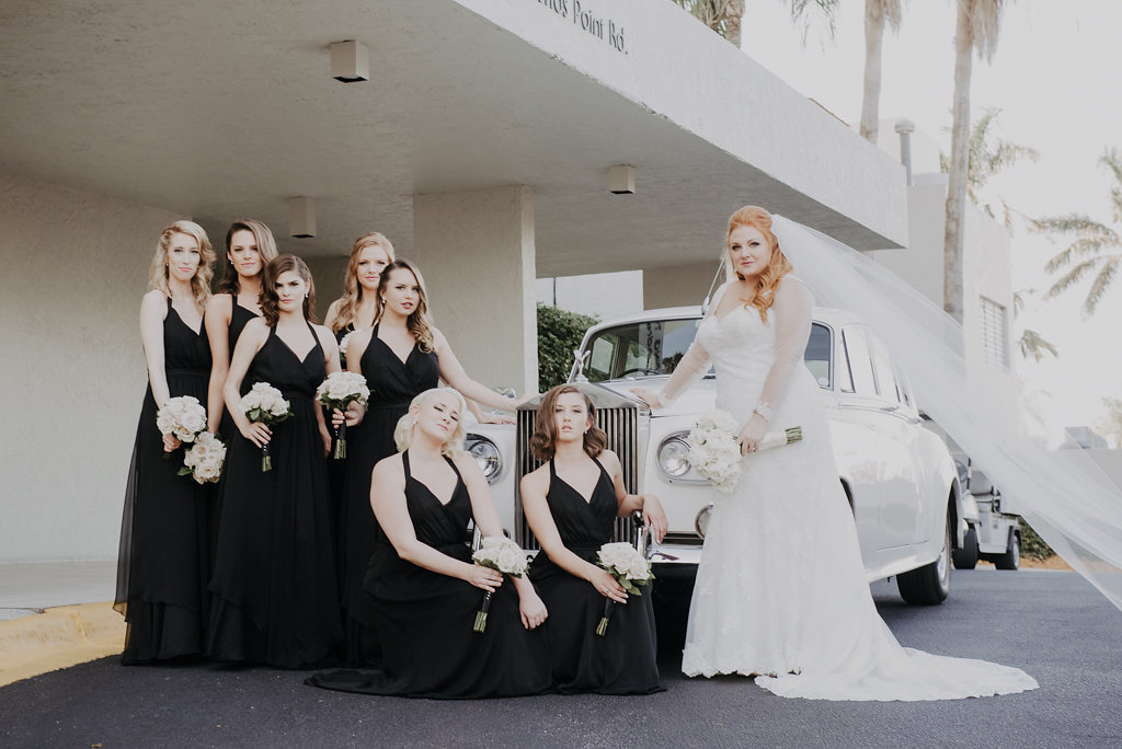 Outdoor Bridal Party Portrait with Antique Car, Bridesmaids in Long Black V Halter Neck Belted Dresses, Bride in Sweetheart Essence of Australia Lace Long Sleeve Wedding Dress with White Rose Bouquet
