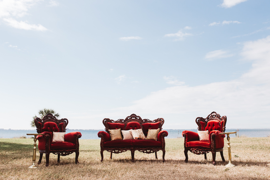 Outdoor Waterfront Wedding 1920s Vintage Glam Inspired Reception Lounge with Antique Plush Red Velvet Chairs and Loveseat and Gold End Tables