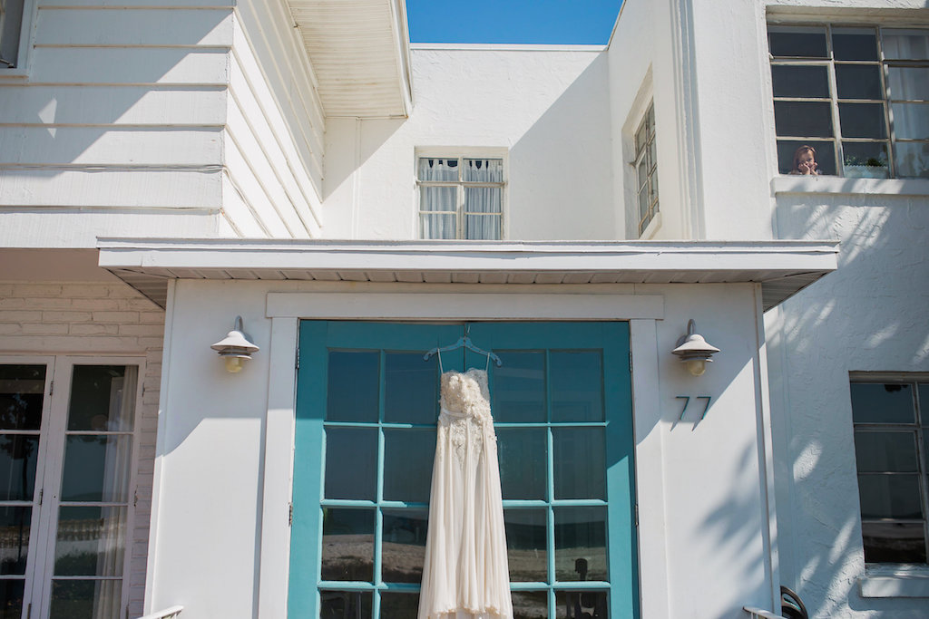 White Wedding Dress with Lace Bodice Hanging in Front of Blue/Teal Door   Venue Sunset Beach Resort