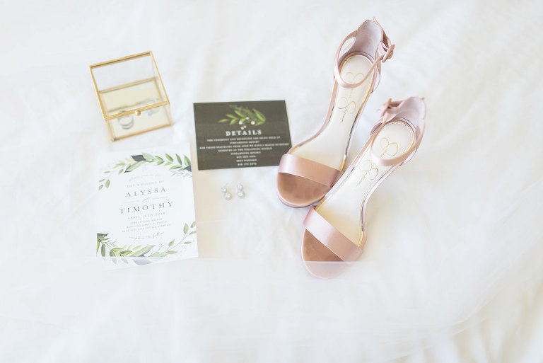 Blush Pink Ankle-Strap Sandal on White Tulle Background Greenery Inspired Invitation Suite Diamond Teardrop Earrings and Gold Clear Jewelry Box with Wedding Bands | Tampa Bay Wedding Photographer Kristen Marie Photography