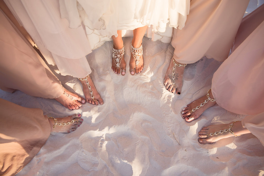 Bridal Party Bridesmaids Sandy Beach Feet with Bead Foot Jewelry on White Sand Wearing Blush Pink Bridesmaid Dresses and Bride in White Wedding Dress