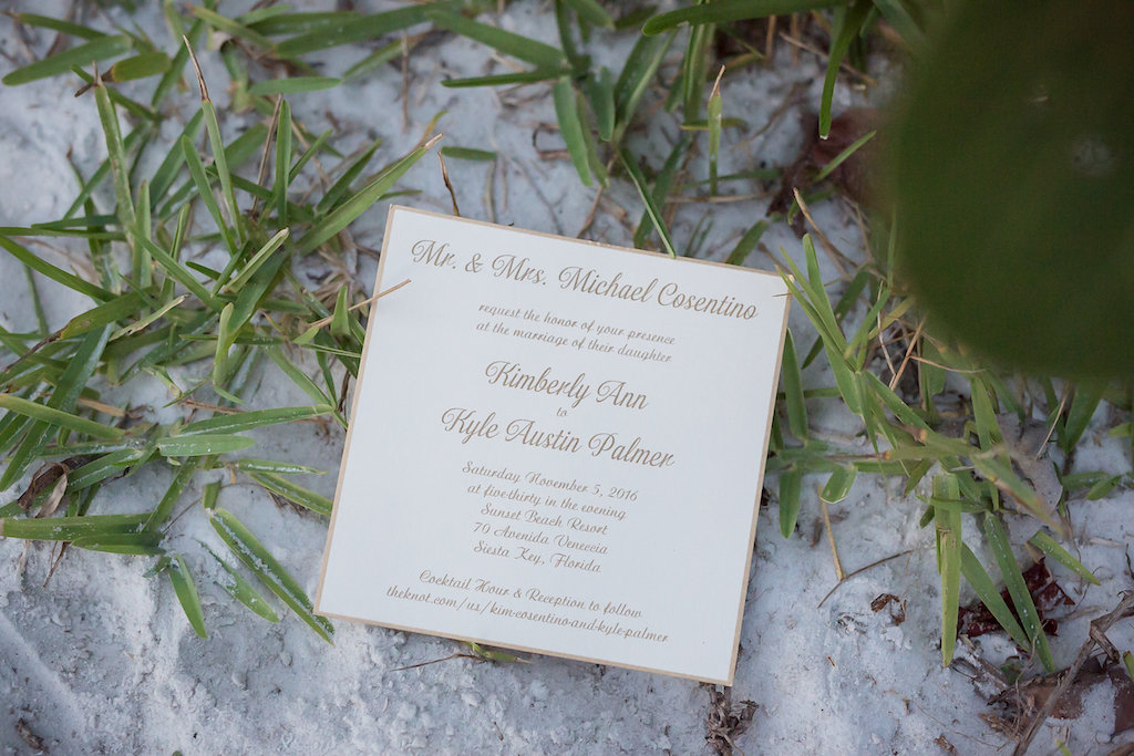 Square Elegant Wedding Invitation with Gold Border and Script Font Laying on Beachy Sand
