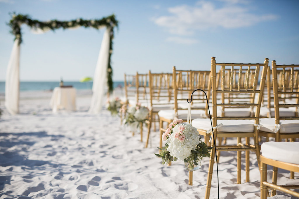 Siesta Key Beach Florida Outdoor Ceremony Setup with Gold Chiavari Chairs White, Pink and green Bouquets on Shepherd Hooks Lined Down the Aisle with Greenery Accented Wedding Arch on Sandy White Beach