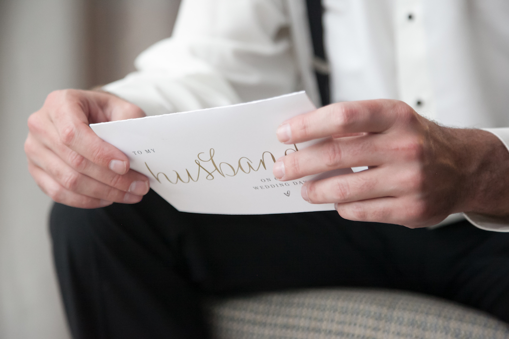 Indoor Groom Getting Ready Wedding Portrait reading Letter from the Bride, White Card with Gold Lettering   Tampa Bay Wedding Photographer Carrie Wildes Photography
