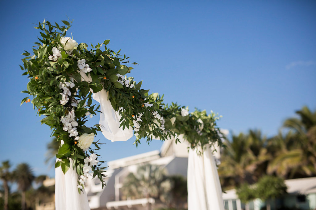 Wedding Arch Outdoors of Greenery Leaves Accented with White Flowers and Orange Berries on White Draping