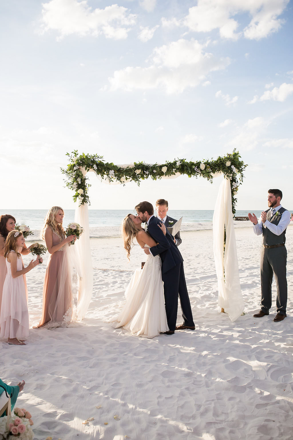 Bride and Groom First Kiss with Ceremony Greenery and White Flower Accented Wedding Arch with White Draping   Outdoor Siesta Key Beach Sarasota Wedding   Cat Pennenga Photography