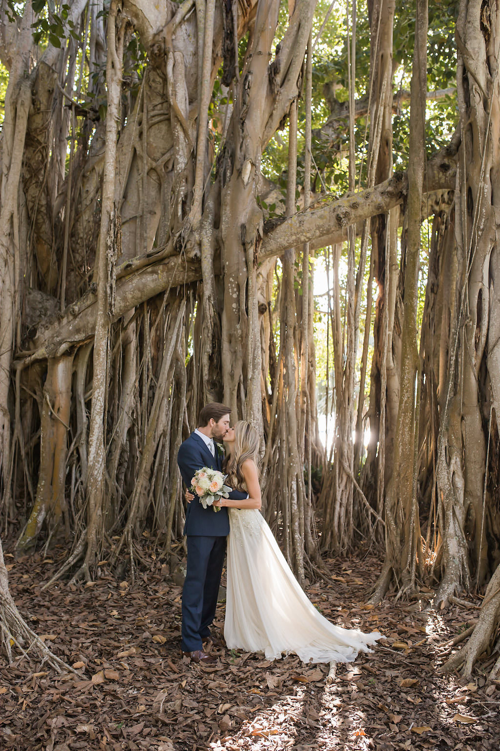 Bride in Floor Length White Wedding Dress Holding White and Pink Bouquet Kissing Groom in Blue Suit with Banyan Tree Backdrop   Sarasota Wedding Photographer Cat Pennenga Photography