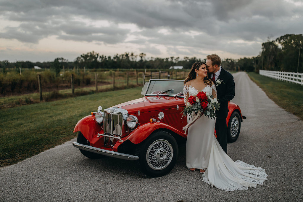 Outdoor Bride and Groom Wedding Portrait, Groom Wearing Navy Blue Suit with Grey Vest, Red Satin Tie and White Flower and Greenery Boutonniere, Bride in Long Sleeve Lace David's Bridal Wedding Dress, and Red Peonies, White Roses and Greenery Bouquet in Vintage Red Convertible Car | Tampa Bay Wedding Photographer Rad Red Creative | Lithia Rustic Wedding Venue Southern Grace