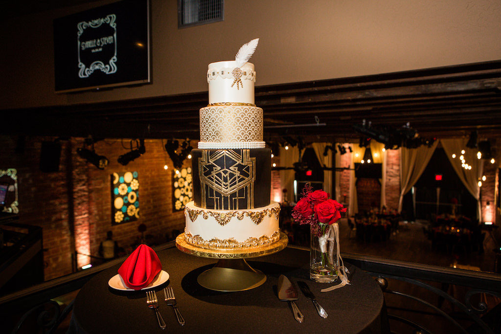 Four Tier Round Great Gatsby Inspired Wedding Cake with Gold and Black Detailing and White Feather, Red Roses Bouquet | St. Pete Wedding Bakery The Artistic Whisk