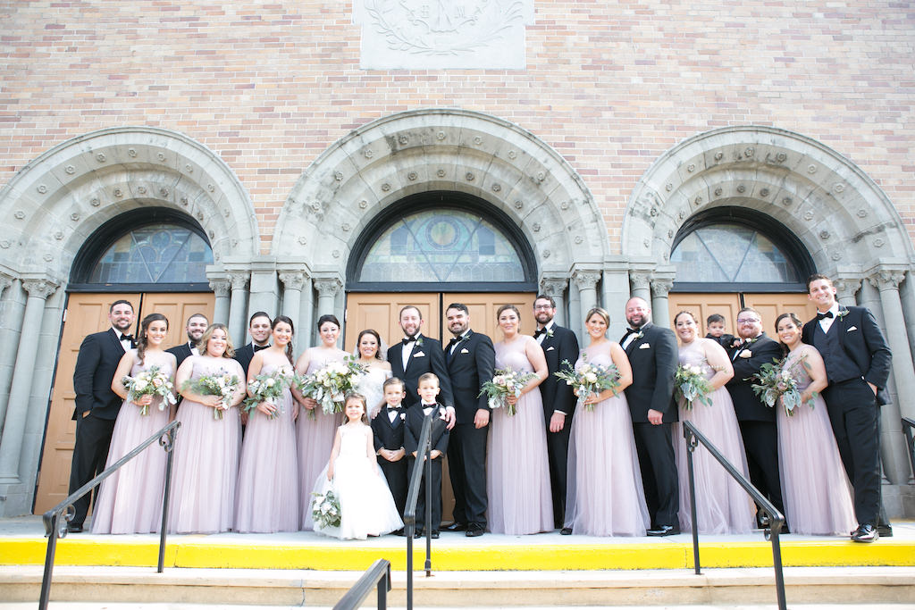 Outdoor Church Step Wedding Party Portrait, Groom and Groomsmen in Black Tuxedo with Bow Tie and Blush Rose Boutonniere, Bridesmaids in Matching Jenny Yoo Strapless Mauve Layered Dresses, Flower Girl in White Dress, with White Rose and Greenery Bouquet   Tampa Bay Wedding Photographer Carrie Wildes Photography   Venue Our Lady of Perpetual Help Catholic Church   Dress Shop Bella Bridesmaids