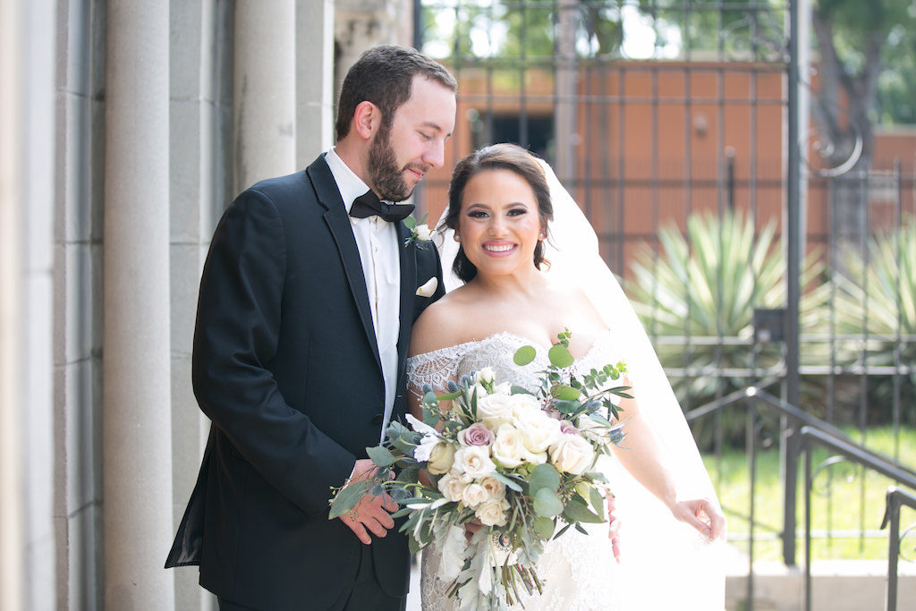 Outdoor Church Steps Wedding Portrait, Bride in Off The Shoulder Lace Augusta Jones Dress with Cream, Blush, Mauve Rose and Thistle Bouquet with Greenery, Groom in Black Tux with Bow Tie and Pink Pocket Square | Tampa Bay Wedding Photographer Carrie Wildes Photography