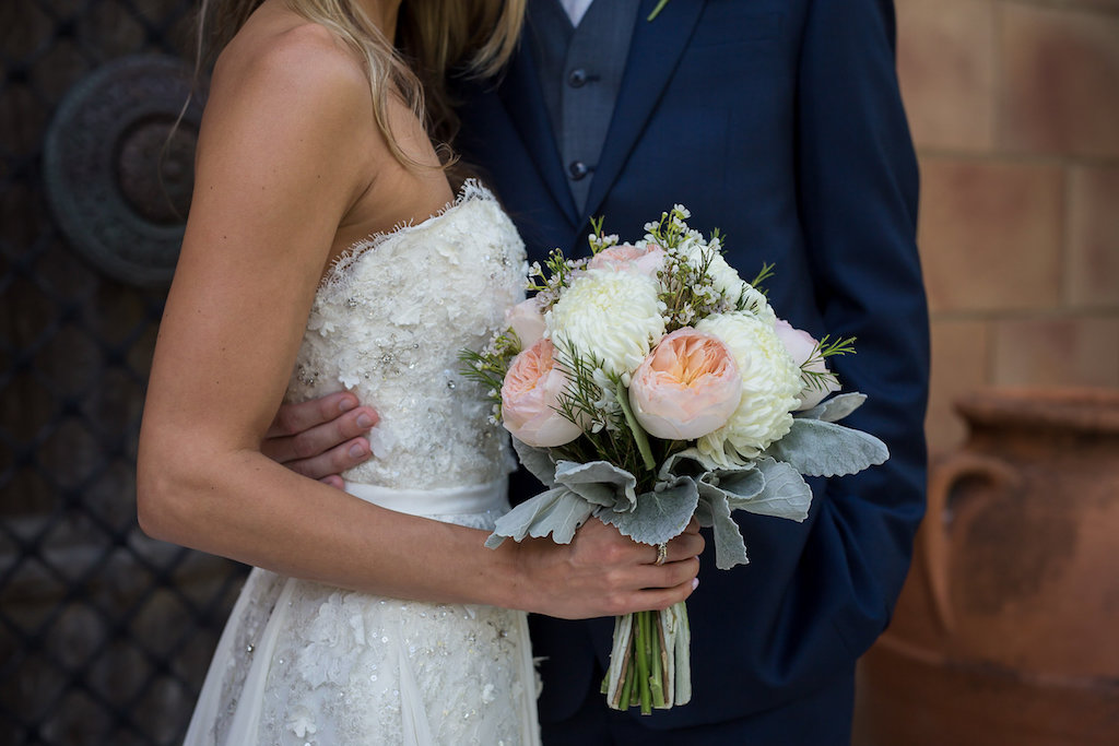 Bride Wearing White Beaded Lace Bodice with Ribbon Belt Wedding Dress Holding Pink Peonies, White Flowers, Greenery and Dusty Miller Bouquet and Groom Holding Brides Waist
