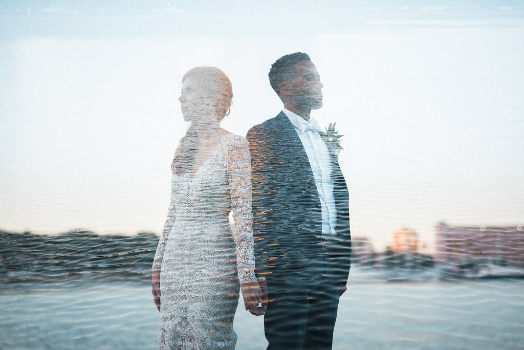 Waterfront Outdoor Off-White Lace Long Sleeve Peek-A-Boo Back Vintage Inspired Bridal Portrait, with Blush Pink Roses and Greenery Organic Bouquet and Groom Wearing Navy Blue Tuxedo, Bow Tie and Organic Boutonniere with Water Feature Overlay | Downtown St. Pete Wedding Photographer Kera Photography